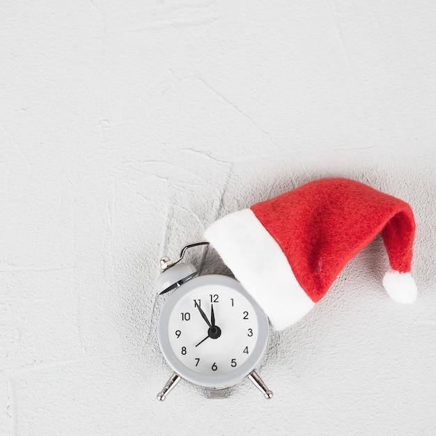 Relógio de natal no chapéu de papai noel Foto gratuita