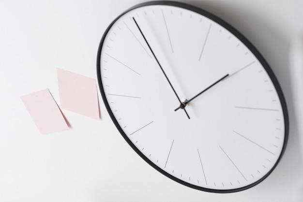 Relógio de parede redondo e adesivos rosa em branco Foto Premium