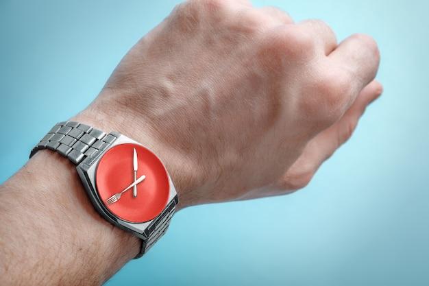 Relógio de pulso na mão do homem. prato, faca e garfo na face do relógio. conceito de jejum intermitente, hora do almoço Foto Premium