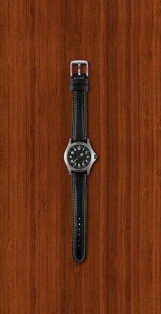 Relógio de pulso preto isolado em fundo escuro de madeira Foto Premium