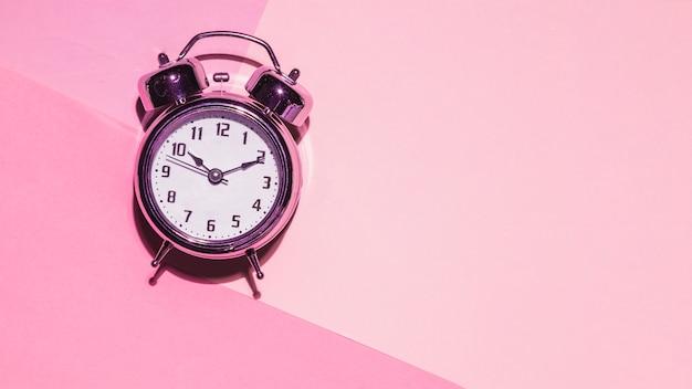 Relógio de vista superior em fundo rosa Foto gratuita