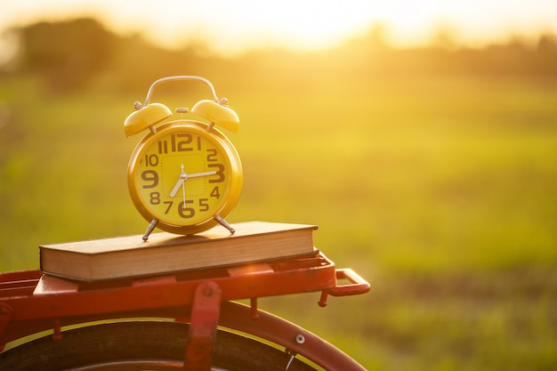 Relógio despertador amarelo e livro colocar na bicicleta clássica estilo vermelho japão Foto Premium