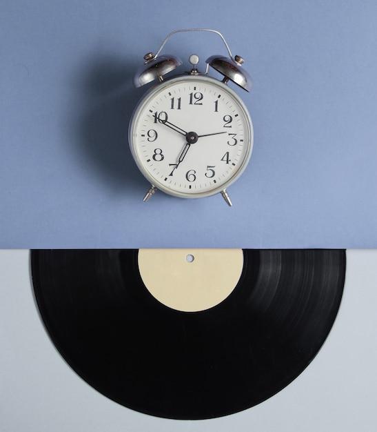 Relógio despertador, disco de vinil em fundo cinza azul. estilo retrô. vista do topo Foto Premium