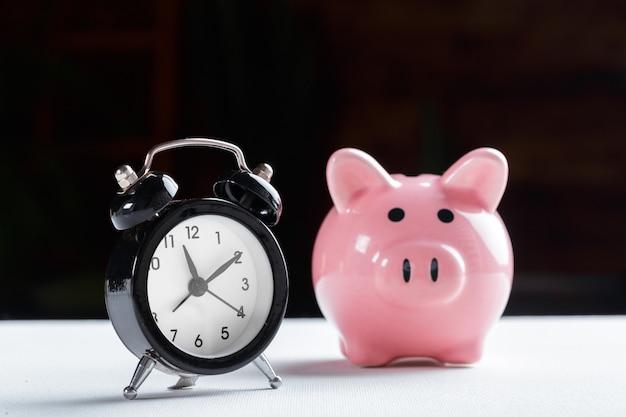 Relógio despertador e cofrinho conceito para poupar tempo Foto Premium