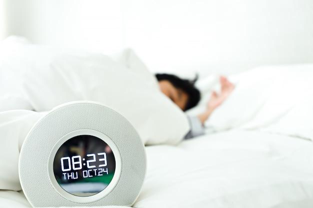 Relógio despertador e menino dormindo no quarto Foto Premium