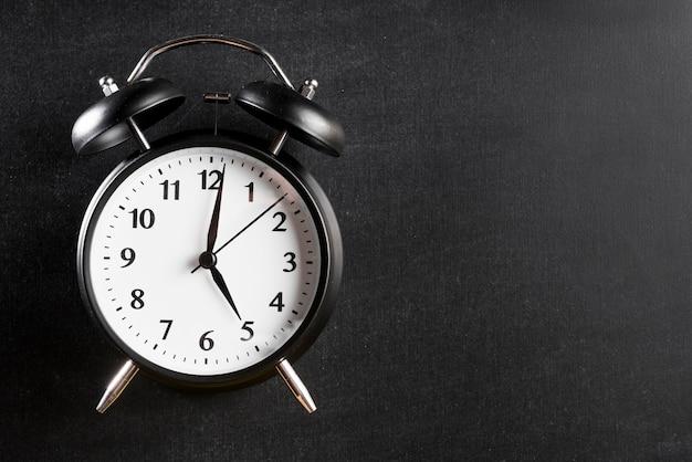 Relógio despertador, mostrando, 5'o, relógio, contra, experiência preta Foto gratuita