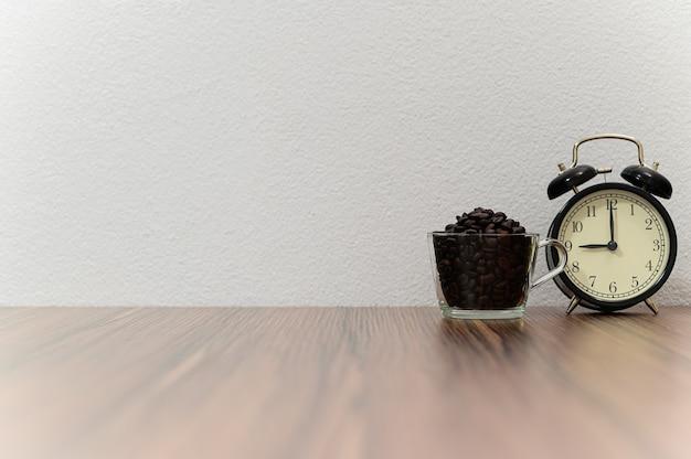 Relógio e grãos de café colocados na mesa Foto Premium