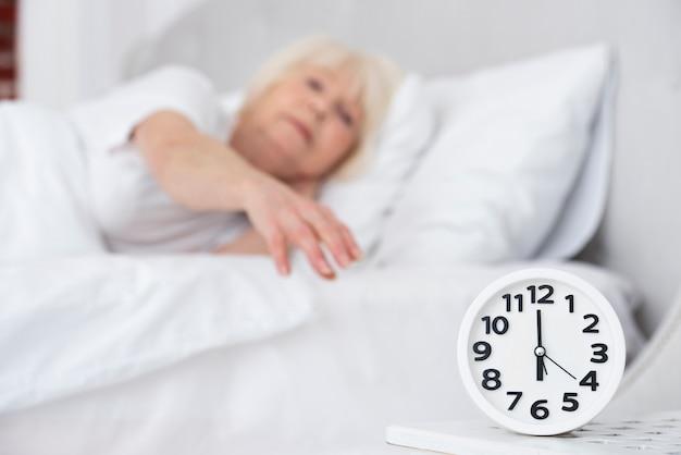 Relógio e mulher mais velha adormecida em fundo Foto gratuita