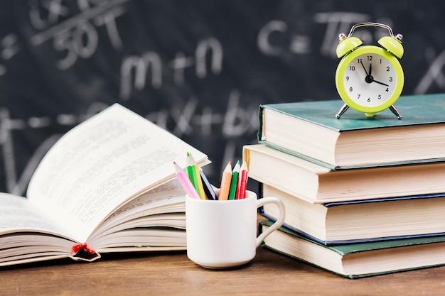 Relógio em cima de livros didáticos na mesa do professor Foto gratuita