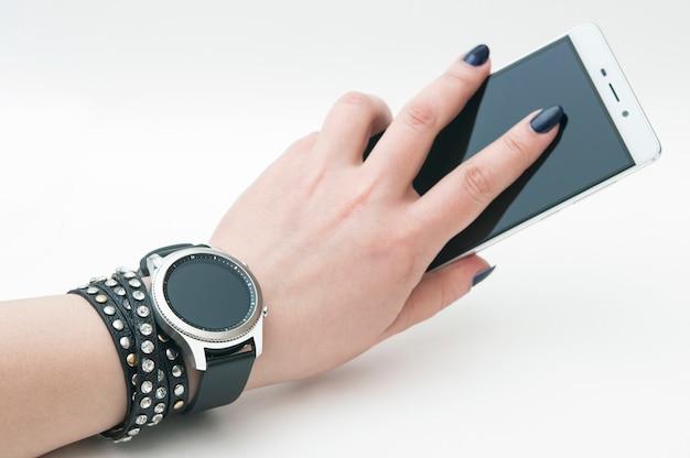 Relógio esperto na mão com um smartphone, isolado no fundo branco. Foto Premium