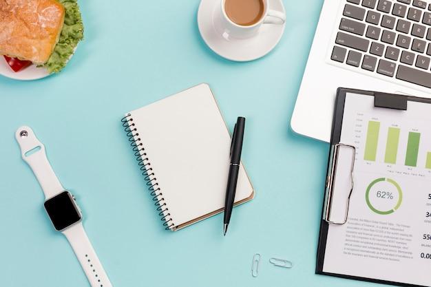 Relógio inteligente branco, artigos de papelaria, sanduíche, prancheta com plano de orçamento e laptop na mesa de escritório azul Foto gratuita