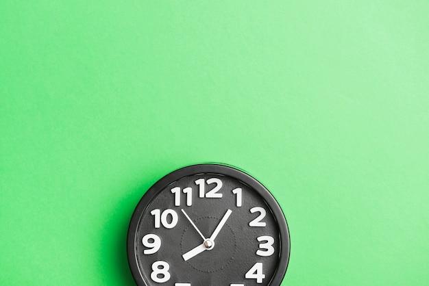 Relógio preto circular no cenário de parede verde Foto gratuita