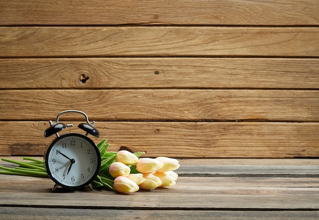 Relógio preto e tulipa na mesa. Foto Premium