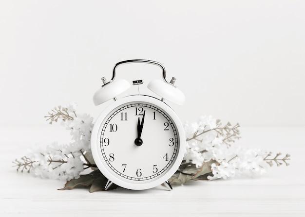 Relógio vintage com flores brancas Foto gratuita