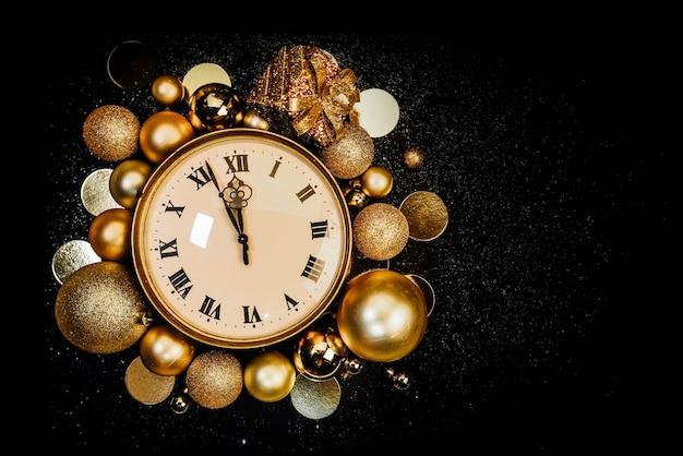 Relógio vintage dourado decorado com bolas de natal em um fundo preto em brilhos. doze horas, o ano novo está chegando. copie o espaço. Foto Premium
