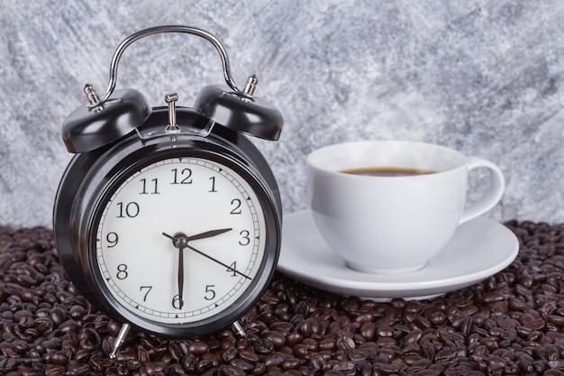 Relógio vintage e café na xícara (conceito de hora do café) com fundo de parede Foto Premium