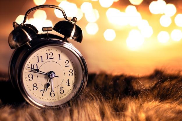 Relógio vintage na pele macia em um quarto com bokeh de luz bonita Foto Premium