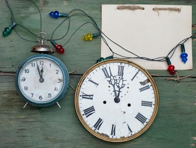 Relógios antigos e bloco de notas artesanal na superfície de madeira verde Foto Premium