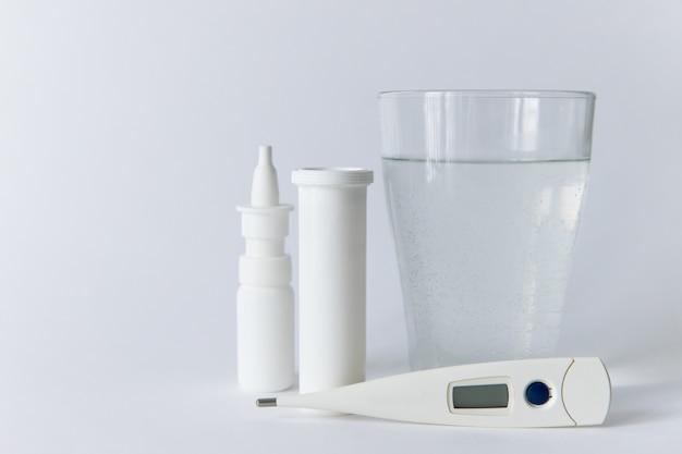 Remédio para spray nasal, frasco de comprimidos branco, termômetro digital médico, vidro Foto Premium