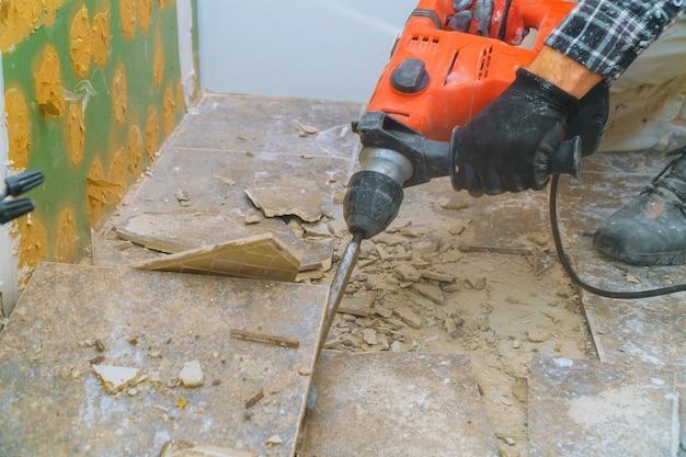 Remoção do piso antigo durante uma renovação de habitação de martelo de demolição, fragmentos de telhas cerâmicas Foto Premium