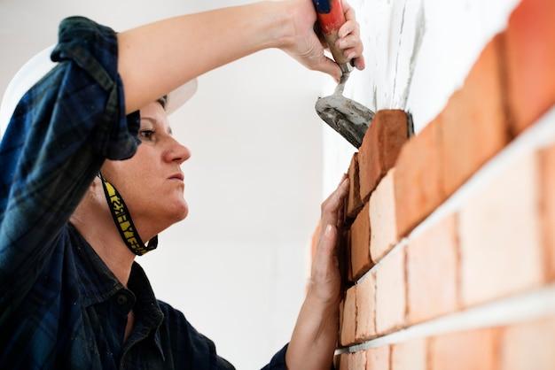 Reparação de construção de construtor de reboco na parede Foto gratuita