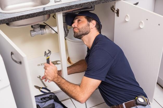 Reparação de encanador sob a pia Foto Premium