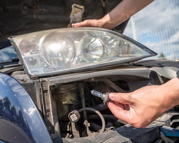 Reparação de faróis de automóveis substituindo lâmpadas por novas Foto Premium