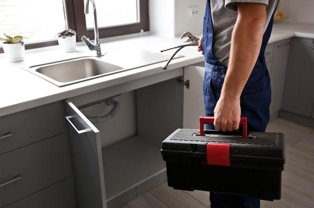 Reparador chegou ao cliente para corrigir alguns problemas na cozinha Foto Premium