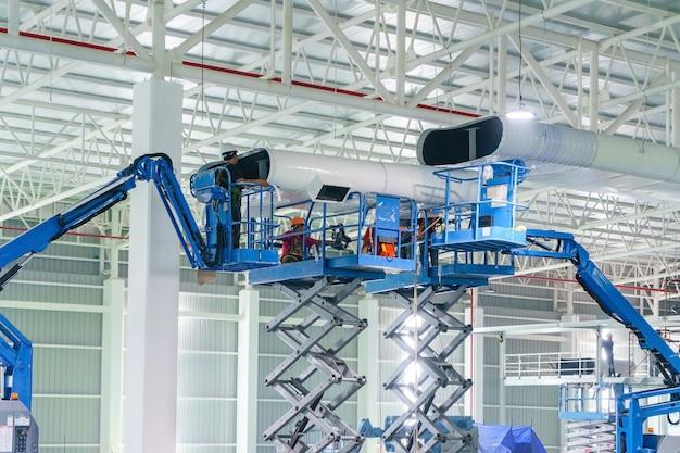 Reparador de construtor instalar tubos de ventilação e dutos de hvac pendurados no teto Foto Premium