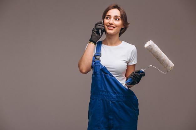 Reparador de mulher com rolo de pintura isolado falando ao telefone Foto gratuita