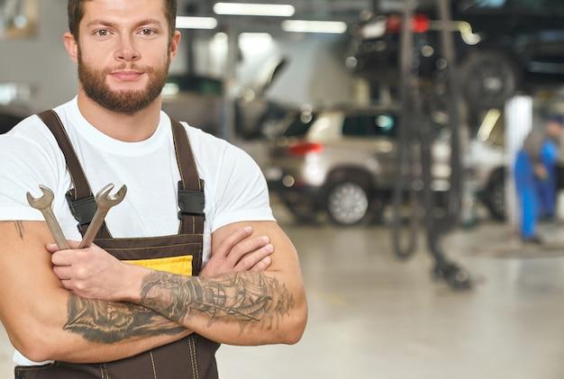 Reparador musculoso e tatuado posando em serviço automático. Foto gratuita