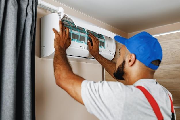 Reparador profissional instalando ar condicionado em uma sala Foto Premium