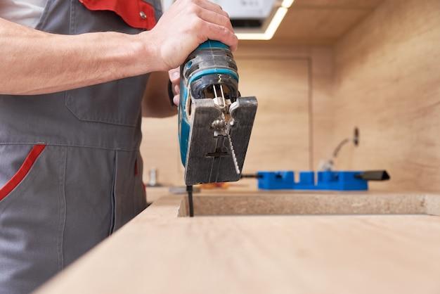 Reparador usando quebra-cabeças elétrico. local de serração para instalação de fogão a gás em uma bancada Foto Premium