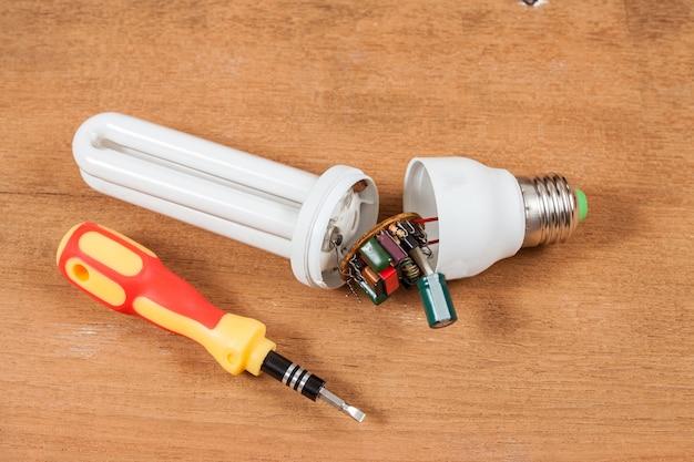 Reparar lâmpadas de poupança de energia na mesa de madeira. Foto Premium