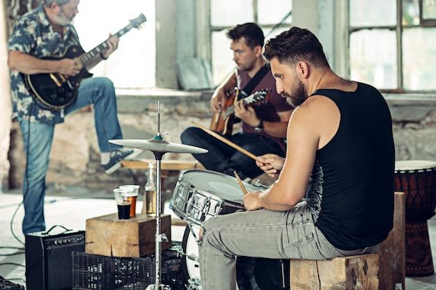 Repetição de banda de rock. guitarrista e baterista atrás da bateria. Foto gratuita