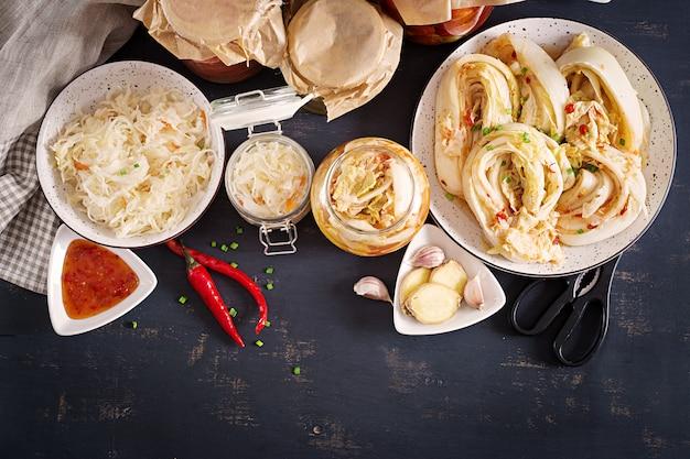 Repolho kimchi, tomate marinado, frascos de vidro azedo chucrute sobre a mesa da cozinha rústica. Foto gratuita