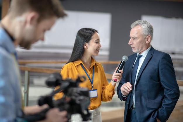 Repórter asiática segurando um microfone na mão enquanto fala com um empresário Foto Premium
