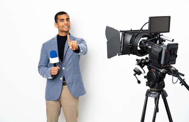 Repórter homem afro-americano segurando um microfone e reportar notícias sobre parede branca isolada, mostrando e levantando um dedo Foto Premium
