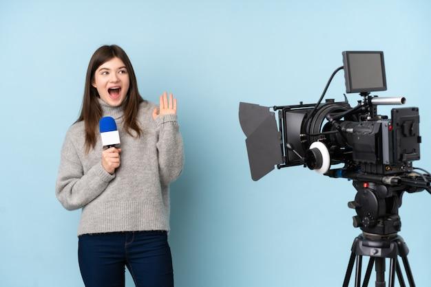 Repórter jovem mulher segurando um microfone e reportar notícias com expressão facial de surpresa Foto Premium
