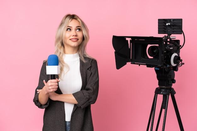 Repórter mulher com uma câmera pensando Foto Premium