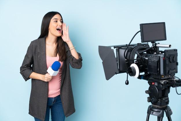 Repórter mulher segurando um microfone e reportando notícias na parede azul gritando com a boca aberta para a lateral Foto Premium