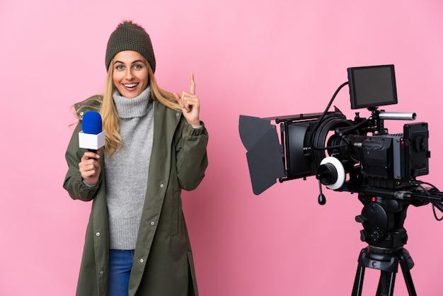 Repórter mulher segurando um microfone e reportando notícias sobre parede rosa apontando para cima uma ótima idéia Foto Premium