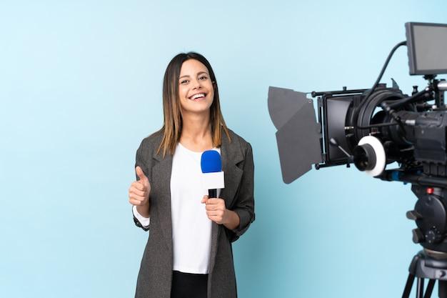 Repórter mulher segurando um microfone e reportar notícias sobre parede azul isolada, dando um polegar para cima gesto Foto Premium