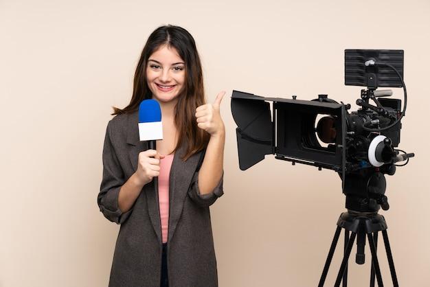 Repórter mulher segurando um microfone e reportar notícias sobre parede dando um polegar para cima gesto Foto Premium
