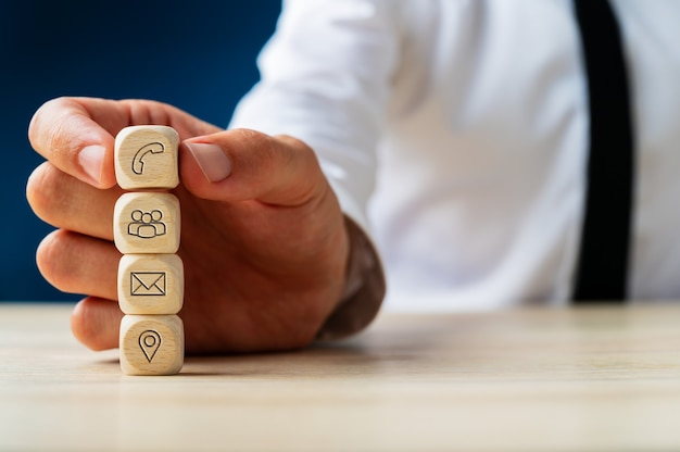 Representante do serviço ao cliente empilhando dados de madeira com ícones de contato e informações sobre eles. Foto Premium