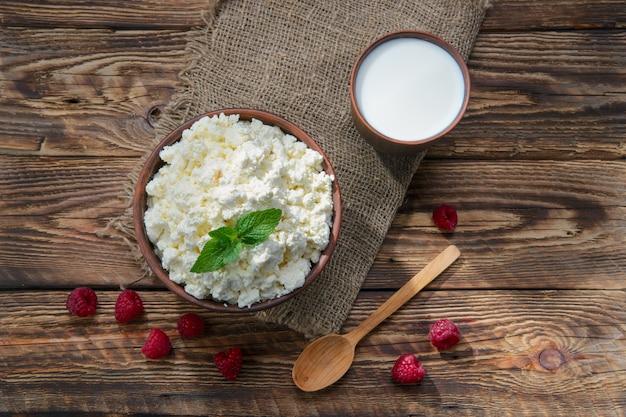 Requeijão e leite em clayware na mesa de madeira Foto Premium