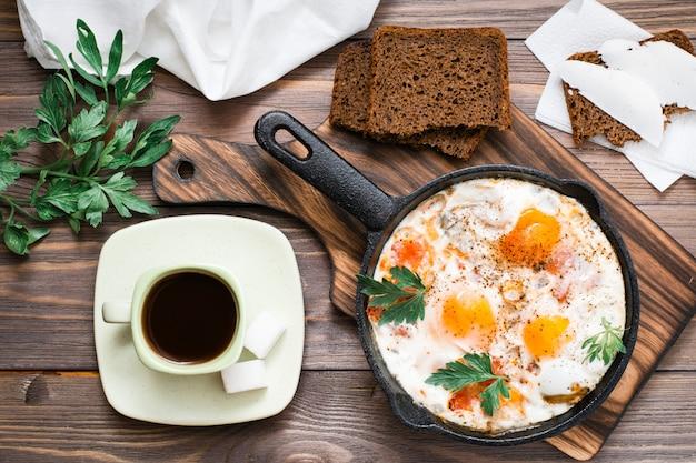Reshakshuka de ovos fritos com tomate e salsa em uma panela Foto Premium