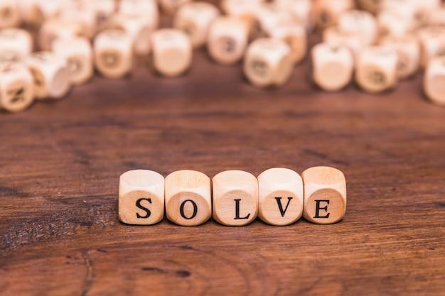 Resolver palavra sobre cubos de madeira sobre a mesa marrom Foto gratuita