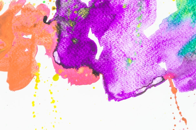 Respingo da aguarela colorida no fundo branco Foto gratuita