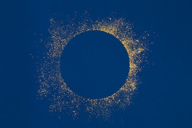 Respingo de glitter dourados círculo com centro vazio sobre fundo azul. Foto Premium